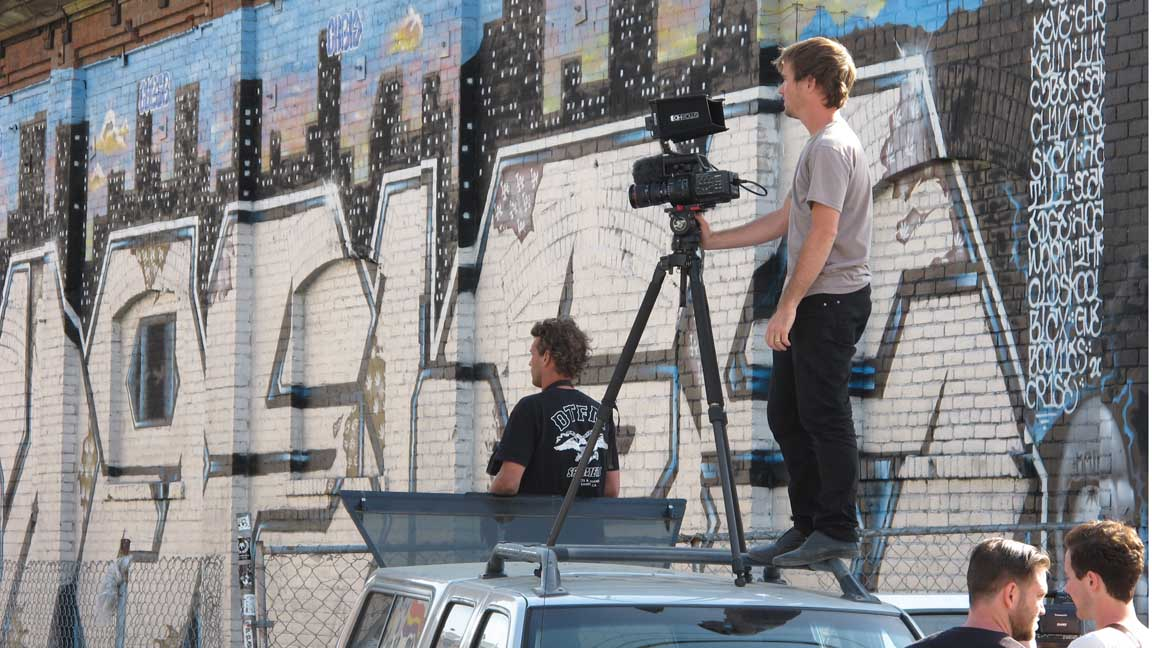 russell stands on the van to film Tom