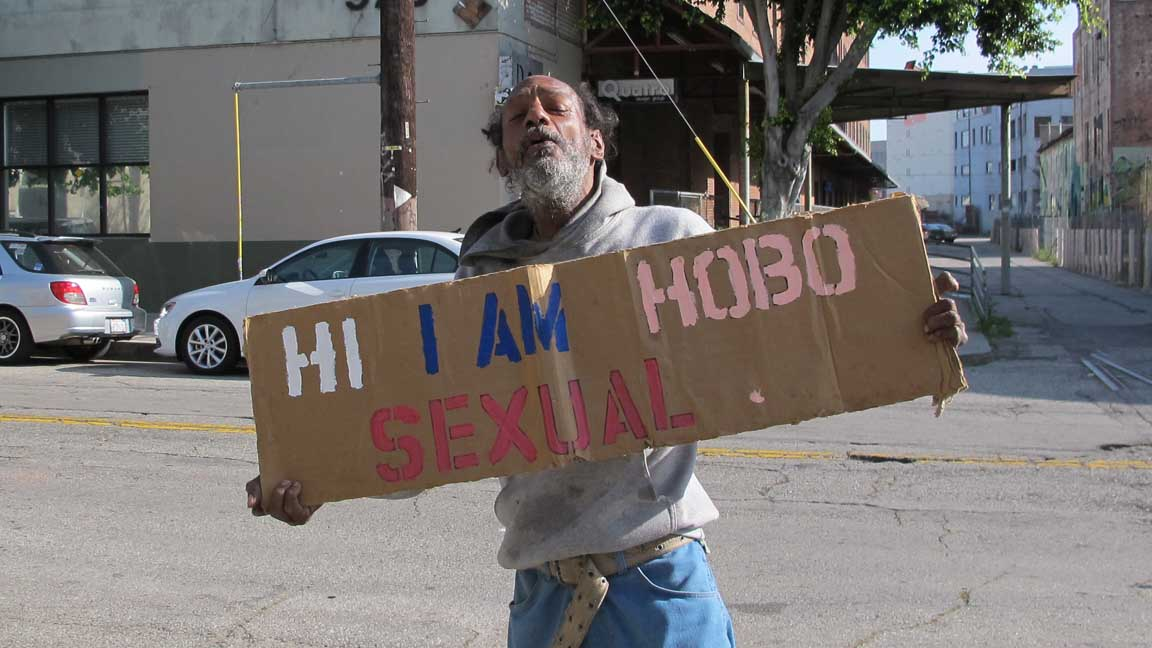a man holds a sign that reads I am a hobo sexual