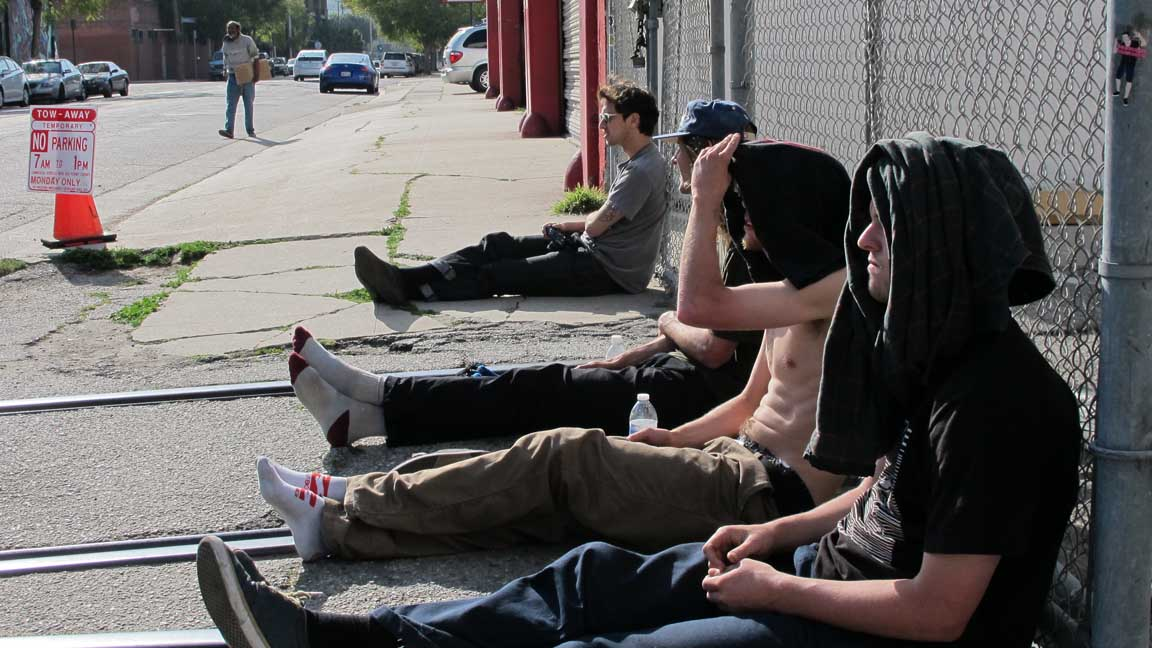 dudes sitting while tom skates