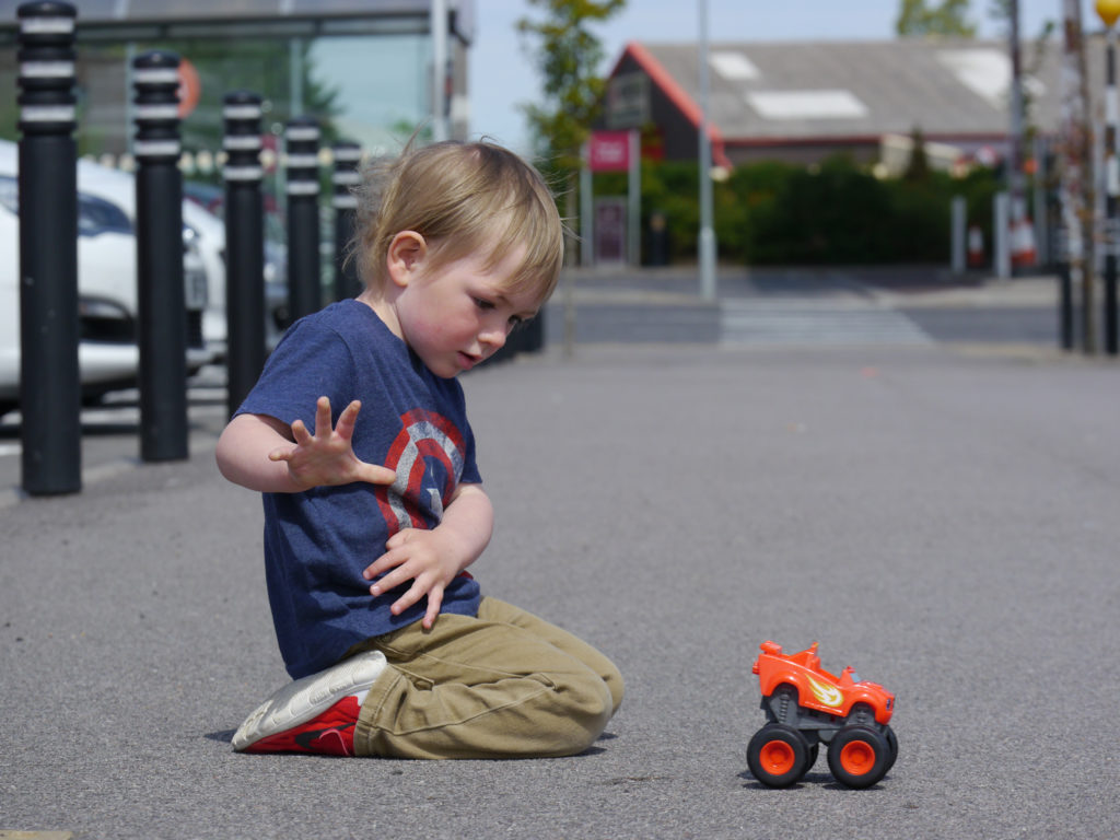 Ivor kneels on the asphalt floor of the Sainsbury's car park testing his new Blaze Monster Truck toy . It is a sunny day in Nairn.
