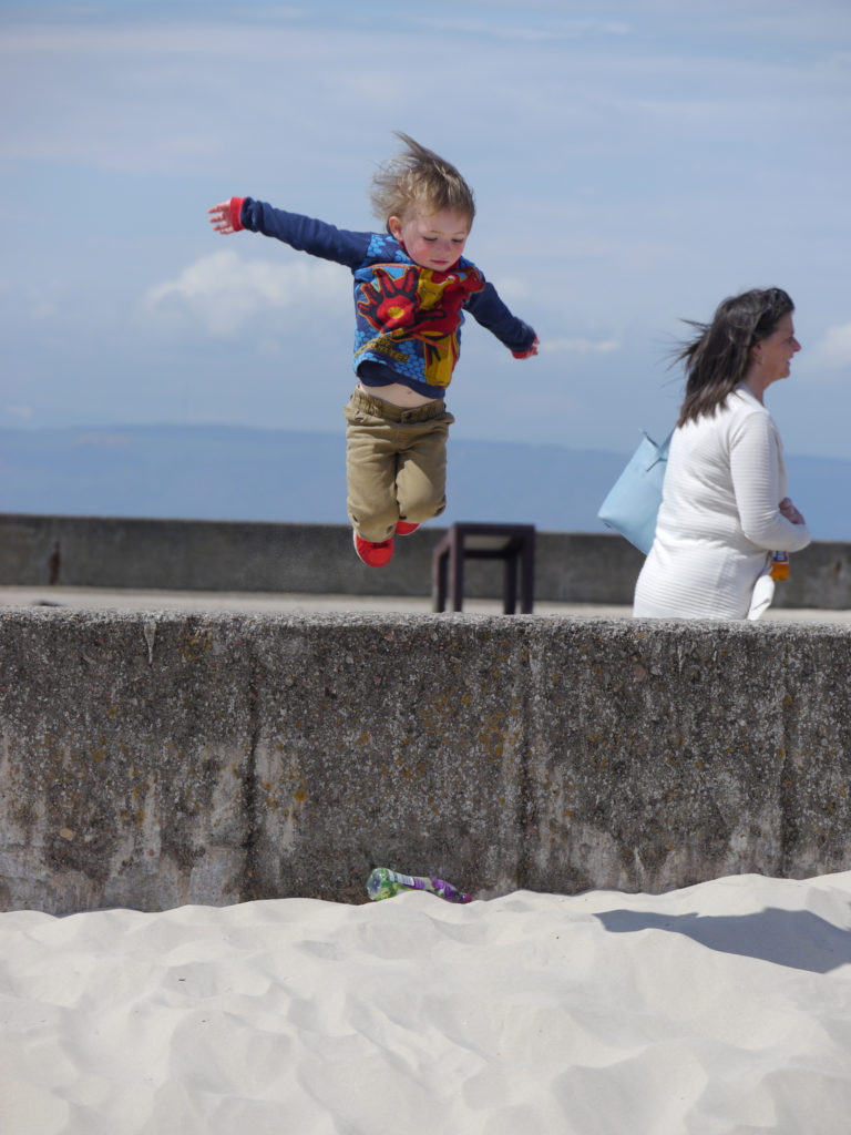Ivor leaps off the pier wall onto the white sand of Nairn beach.